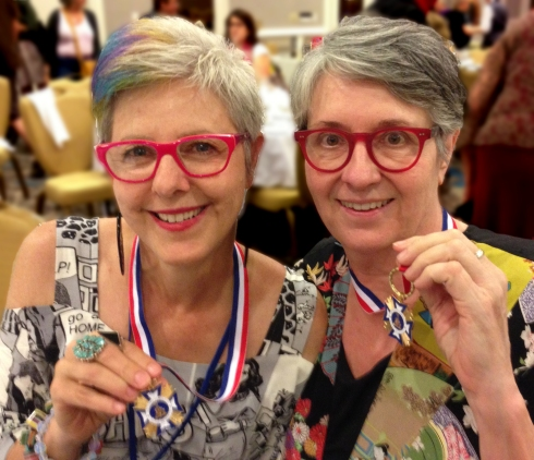 Cheri Gaulke and Sue Maberry display medals from the Veteran Feminists of America